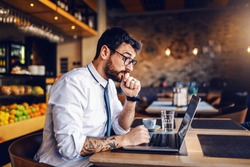 Young focused Caucasian bearded businessman with tattoo and eyeglasses in shirt and tie sitting in cafe and reading important e-mail from client.