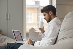 Young focused european businessman drinking tea or coffee from cup and watching business graph on laptop. Concept of modern successful man. Bearded stylish guy wearing suit. Office interior. Daytime