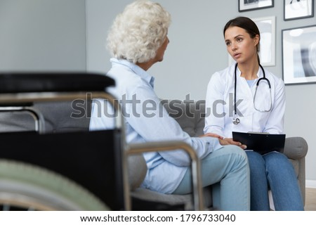 Young focused nurse visiting mature middle aged disabled patient for rehabilitation therapy at home. Skilled attentive millennial physiotherapist consulting senior old woman, healthcare concept.