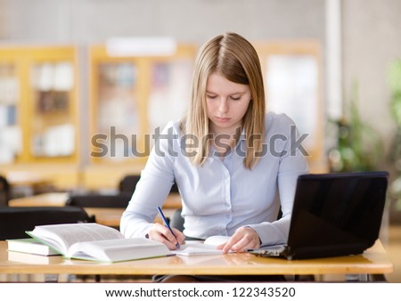Young focused student using computer in a library