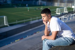 Young football fan bored while sitting on stadium bleachers