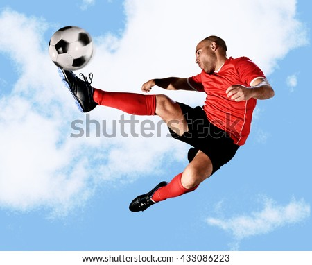 young football player kick ball in skillful volley jumping on the air in dynamic pose wearing red jersey and socks isolated on blue sky background shot in sport advertising style