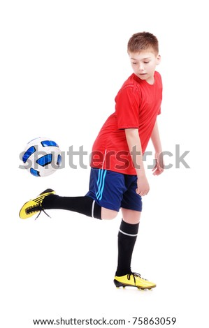 Young football player playing with a ball on white background