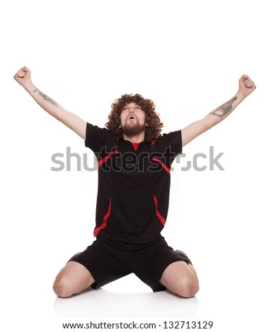 young football player with tattos in his arms celebrating the goal with open arms isolated on white background - stock photo