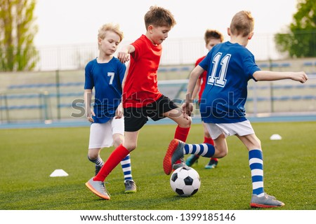 Young Football Players Kicking Ball on Soccer Field. Soccer Horizontal Background. Youth Junior Athletes in Red and Blue Soccer Shirts
