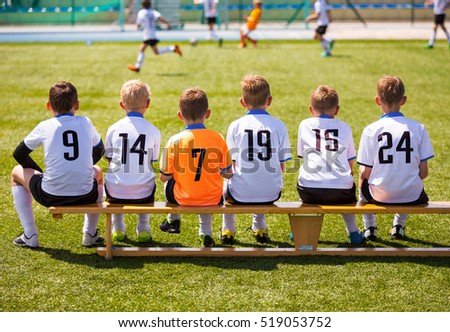 Young Football Players. Young Soccer Team Sitting on Wooden Bench. Soccer Match For Children. Young Boys Playing Tournament Soccer Match. Youth Soccer Club Footballers