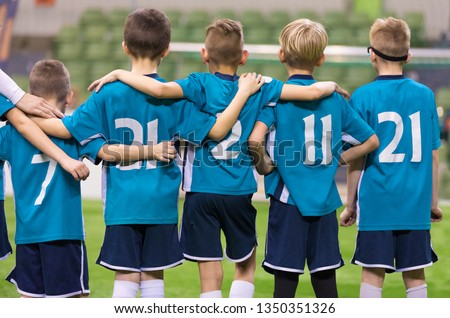 Young Football Players. Young Soccer Team Supporting Friends During Penalty Kicks. Soccer Match For Children. Young Boys Playing Tournament Soccer Match. Youth Soccer Club Footballers