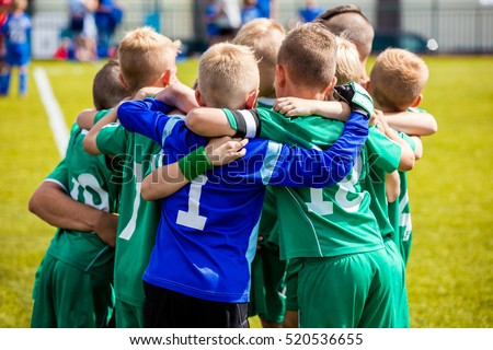 Young football soccer players in sportswear. Young sports team with football coach. Pep talk with coach before the final match. Soccer school tournament