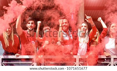 Young football supporter fans cheering with colored smoke watching soccer match together at stadium - Friends people group with red t-shirts having excited fun on sport world championship concept - Shutterstock ID 1071651677