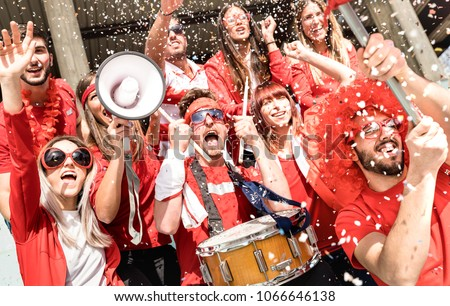 Young football supporter fans cheering with flag and confetti watching soccer match at stadium - Friends people group with red t-shirts having excited fun on sport world championship concept #1066646138