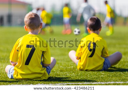 Young football team wearing sports yellow soccer dress. Soccer players on sports field. Football soccer match for children. Youth sports team sitting together and watching football soccer game.