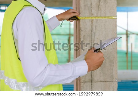 young foreman builder, engineer or inspector checking and inspecting with clipboard and measuring tape at construction site building interior project, inspection, contractor and engineering concept