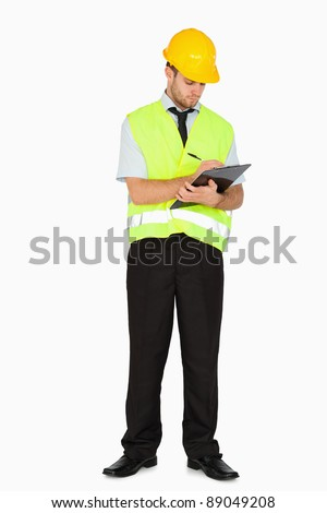 Young foreman in safety jacket taking notes on clipboard against a white background