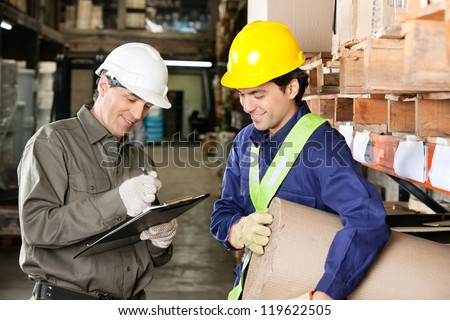 Young foreman looking at supervisor writing notes in warehouse