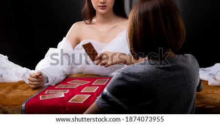 Young Fortune Teller open Tarot Cards in Black Tent and Asian woman pick up card to see future of love and destiny, copy space Stock foto ©