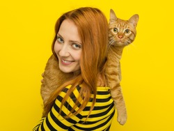 Young foxy woman in yellow cardigan loves her cute ginger cat Cat. Yellow background