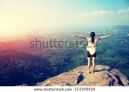 young freedom woman open arms on mountain peak #553398928