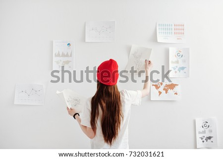 Young freelance designer working on creating infographics - Shutterstock ID 732031621