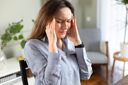 Young freelancer woman suffering with a headache at home office