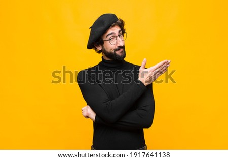 young french artist man feeling confused and clueless, wondering about a doubtful explanation or thought against orange wall Foto stock ©