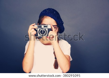 Young french girl taking a picture with a vintage film camera. Young fashion, photography, travel, foreign language learning and life style concept