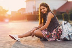 Young fresh cheerful hipster  girl  sitting on the road in countryside wearing stylish summer clothes, bright print skirt , neon  bag pack. Warm evening colors. Sunset. Lifestyle image.