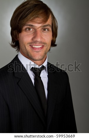 Young fresh confident businessman with longer hair over a greyish background.