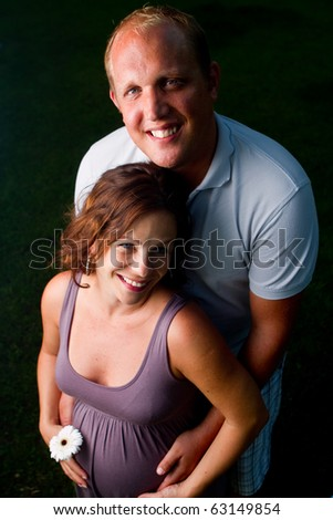 Young fresh happy couple with a pregnant woman. Shot from above - new fresh angle.