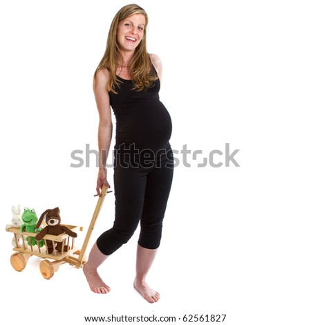 Young fresh pregnant woman is pulling  a trolley filled with toy animals isolated over white background.