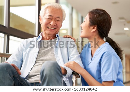young friendly asian female caregiver talking chatting to happy senior man in hallway of nursing home Stock photo ©