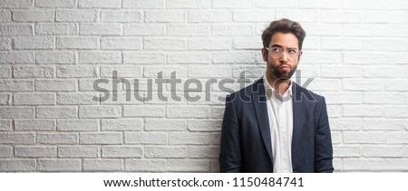 Young friendly business man doubting and confused, thinking of an idea or worried about something Foto stock ©