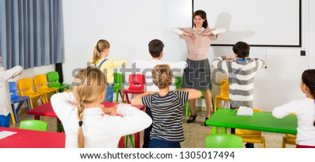 Young friendly female teacher conducting little warm-up with pupils during  break in lesson in elementary school  #1305017494