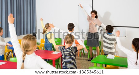 Young friendly female teacher conducting little warm-up with pupils during  break in lesson in elementary school  #1365345611