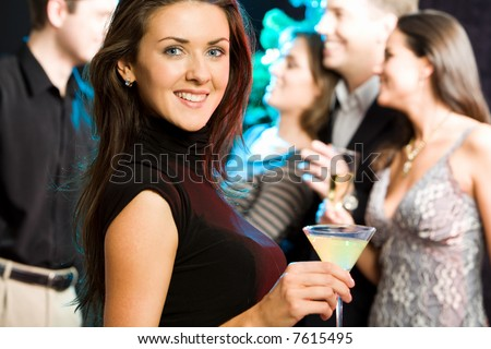 Young friendly woman looking at camera while a party