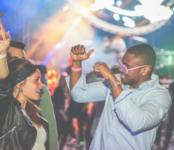 Young friends dancing at party in night club - Soft focus on black man