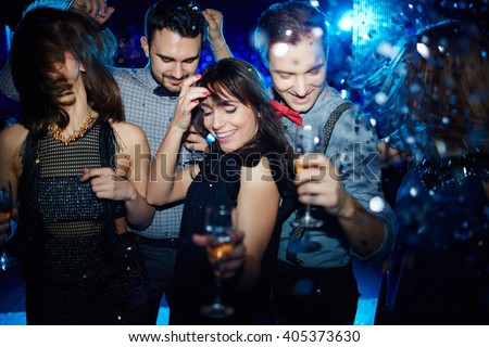 Stock Photo Young friends dancing energetically in nightclub