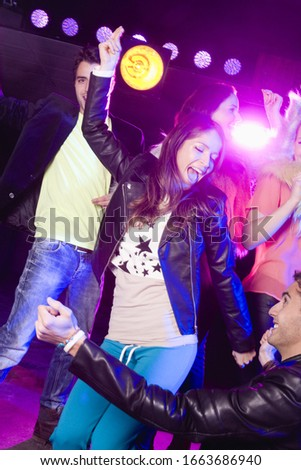 Young friends dancing in nightclub