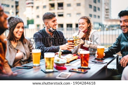Young friends drinking beer pint with open face mask - New normal lifestyle concept with milenials having fun together talking at outside brewery bar - Warm filter with focus on left central guy Stock fotó ©
