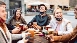 Young friends drinking beer wearing face mask - New normal lifestyle concept with people having fun together talking on happy hour at hipster brewery bar - Bright warm filter with focus on central guy