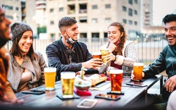 Young friends drinking beer with open face mask - New normal lifestyle concept with milenials having fun together talking at outside brewery bar - Warm filter with focus on left central guy