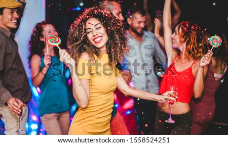 Young friends drinking champagne while dancing inside disco club - Happy people having fun eating candy lollipops at night party - Holidays and nightlife concept - Focus on woman face #1558524251