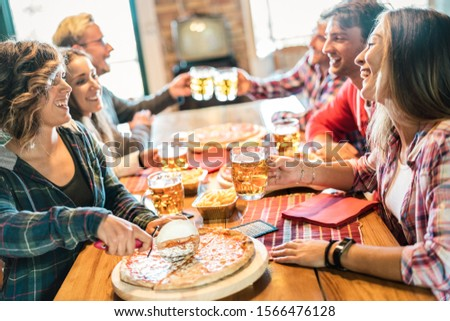 Young friends eating pizza at home on winter reunion - Friendship concept with happy people enjoying time together and having fun drinking brew pints - Cosy dinner place with focus on beer glass stock photo