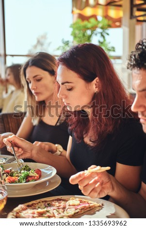 Young friends enjoying pizza and salad in a outdoor cafe #1335693962