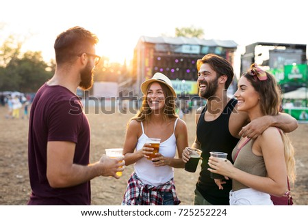 Young friends hanging out and enjoying drinks at music festival #725252224