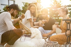 Young friends hanging out together, sitting with a dog, drinking wine and talking. People spending summer time having lunch together at backyard of country house at sunset