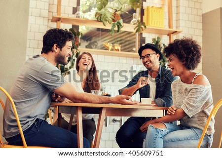 Young friends having a great time in restaurant. Group of young people sitting in a coffee shop and smiling. #405609751