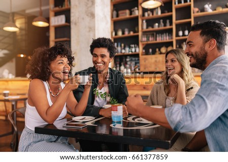 Young friends having a great time in restaurant. Multiracial group of young people sitting in a coffee shop and smiling. Stock photo ©