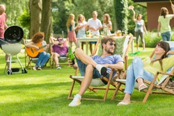 Young friends having barbecue picnic in the nature, playing guitar, playing badminton, enjoying sunny summer day outdoor