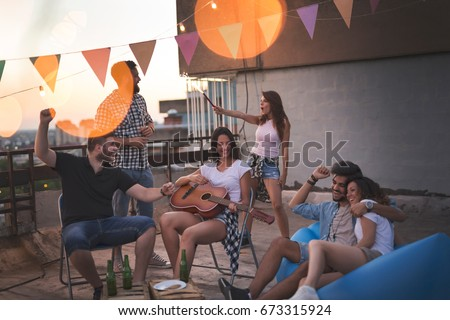 Young friends having fun at a rooftop party, playing the guitar, singing, dancing and chilling out. Focus on the girl playing the guitar