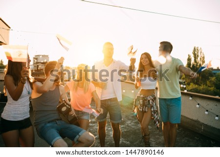 Young friends having fun at a rooftop party, playing the guitar, singing, dancing and drinking #1447890146
